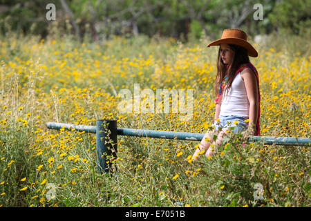 Sullen girl in cowboy hat sitting on fence in field - Stock Photo