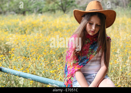 Sullen girl in cowboy hat sitting on fence gazing down - Stock Photo