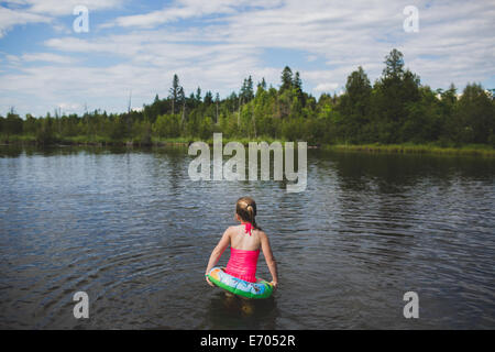 Rear view of girl with rubber ring in Indian river, Ontario, Canada - Stock Photo