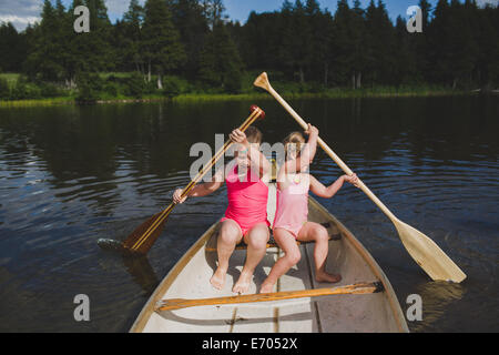 Two young sisters rowing in canoe on Indian river, Ontario, Canada - Stock Photo