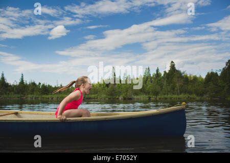 Excited girl sitting in canoe on Indian river, Ontario, Canada - Stock Photo