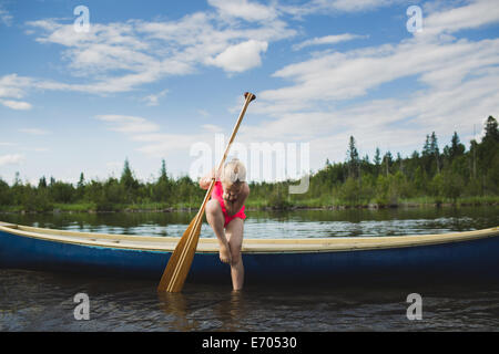 Curious girl looking down at water in Indian river, Ontario, Canada - Stock Photo