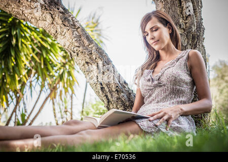 Mid adult woman reading book under palm tree in holiday home garden, Capoterra, Sardinia, Italy - Stock Photo
