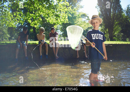 Boy holding fishing net with friends in background - Stock Photo
