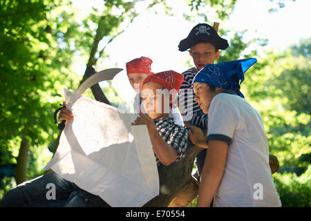 Young boys dressed as pirates, reading map - Stock Photo