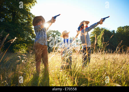 Three young boys dressed as cowboys, holding toy guns - Stock Photo