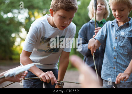 Young boys cooking fish over barbecue - Stock Photo