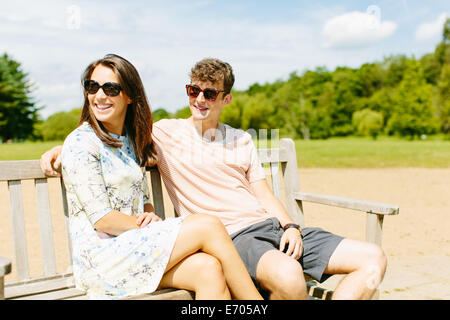 Couple sitting on wooden park bench - Stock Photo