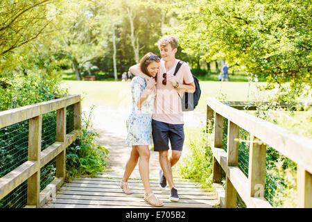 Couple walking over wooden bridge in the park - Stock Photo