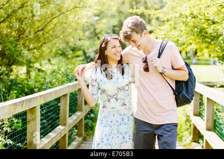 Couple walking over wooden bridge in the park - Stock Photo