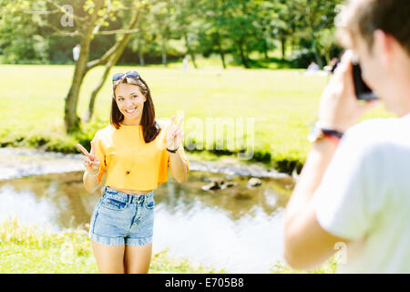 Man taking photo of girlfriend in the park - Stock Photo