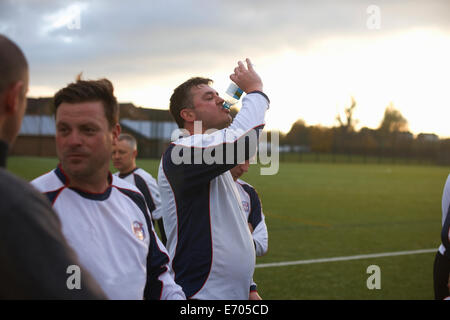 Football players resting and hydrating at half time - Stock Photo