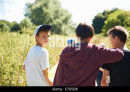 Portrait of boy wearing cap with friends - Stock Photo