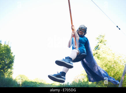Young boy in fancy dress, on zip wire - Stock Photo