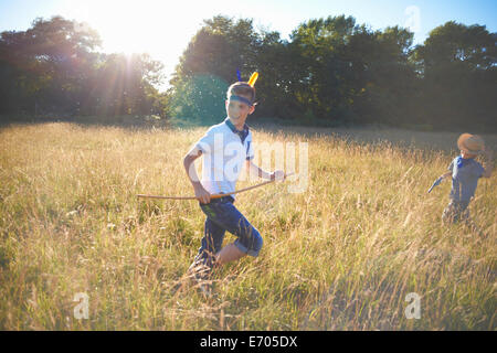 Two young boys playing in a field - Stock Photo