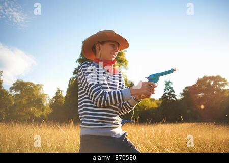 Young boy dressed as cowboy, holding toy gun - Stock Photo