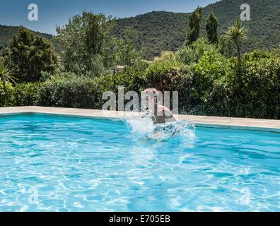 Boy splashing and playing in swimming pool, Capoterra, Sardinia, Italy - Stock Photo