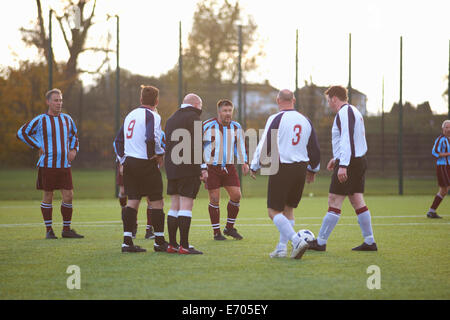 Referee and football players settling dispute - Stock Photo