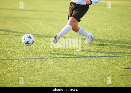 Football player kicking ball - Stock Photo