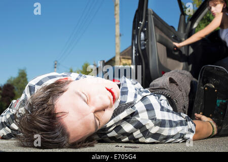 Young man hit by car lying on road - Stock Photo