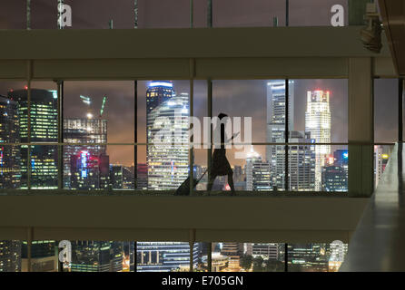 Young woman using smartphone and pulling suitcase, city skyline in view - Stock Photo