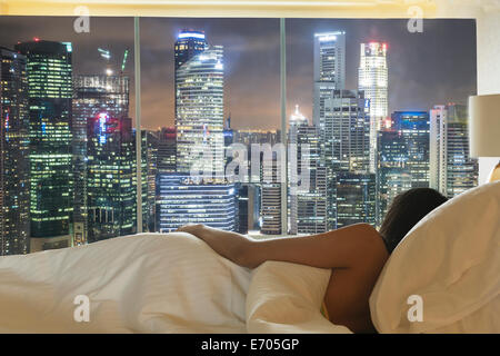 Young woman lying in bed looking at city skyline through window - Stock Photo