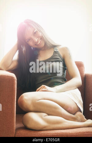 Portrait of young woman sitting in chair, smiling - Stock Photo