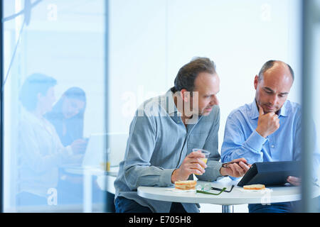 Business people having discussion over lunch - Stock Photo