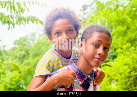 Close up of teenage boy giving friend piggyback ride - Stock Photo