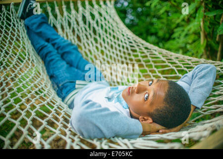 Teenage boy lying in hammock - Stock Photo