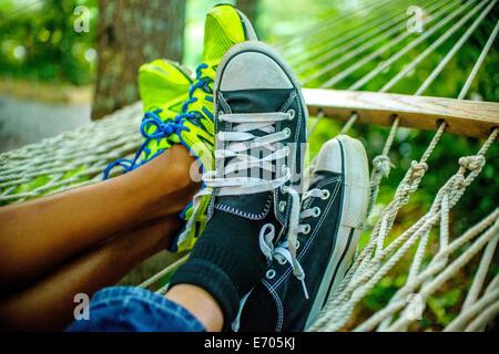 Legs of teenage boys lying in hammock - Stock Photo