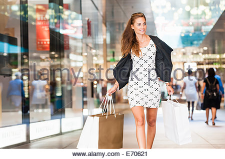 Mid adult woman walking with shopping bags - Stock Photo