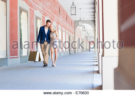 Smiling couple carrying shopping bags in city shopping mall - Stock Photo