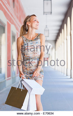 Young woman carrying shopping bags in city shopping mall - Stock Photo