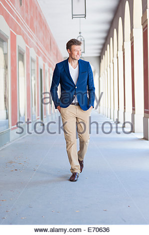 Mid adult male strolling in city shopping mall - Stock Photo