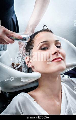 Female hairdresser washing young woman's hair in hair salon - Stock Photo