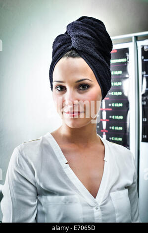 Portrait of young woman in hair salon with towel wrapped around her head - Stock Photo