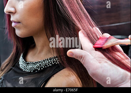 Male hairdresser dyeing young woman's hair pink color in hair salon - Stock Photo