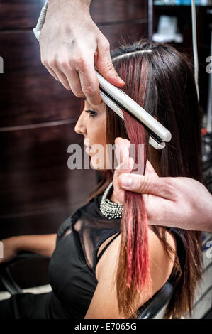 Male hairdresser straightening young woman's hair in hair salon - Stock Photo