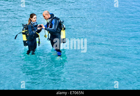 Couple preparing to scuba dive in sea, La Maddalena, Sardinia, Italy Stock Photo