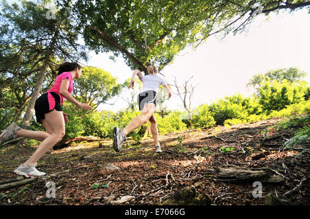 Two young women runners running up forest track - Stock Photo