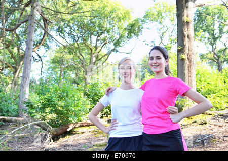 Portrait of two young women runners in forest - Stock Photo