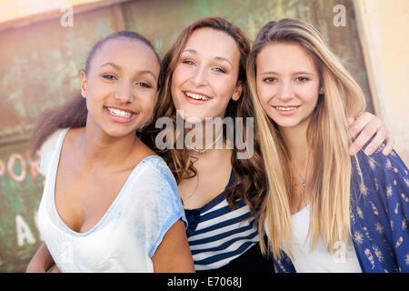Teenage girls, metal door in background - Stock Photo