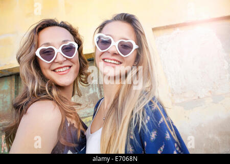 Teenage girls wearing heart-shaped sunglasses - Stock Photo