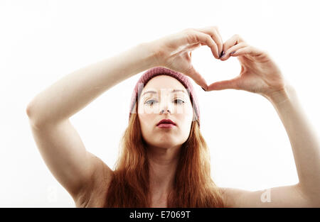 Studio portrait of young woman making heart shape with hands - Stock Photo