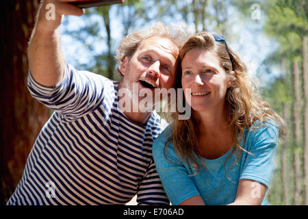Couple taking selfie on smartphone in forest - Stock Photo
