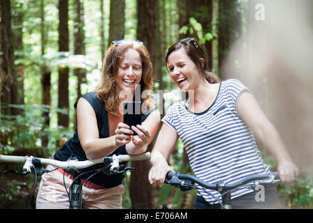 Two women mountain bikers looking at smartphone in forest - Stock Photo