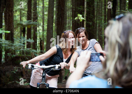 Over shoulder view of women mountain bikers posing for photograph on smartphone in forest - Stock Photo