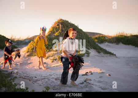 Three children dressed as native american and cowboys running in sand dunes - Stock Photo