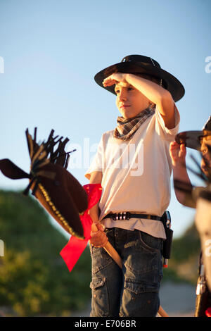 Two boys dressed as cowboys on hobby horses - Stock Photo
